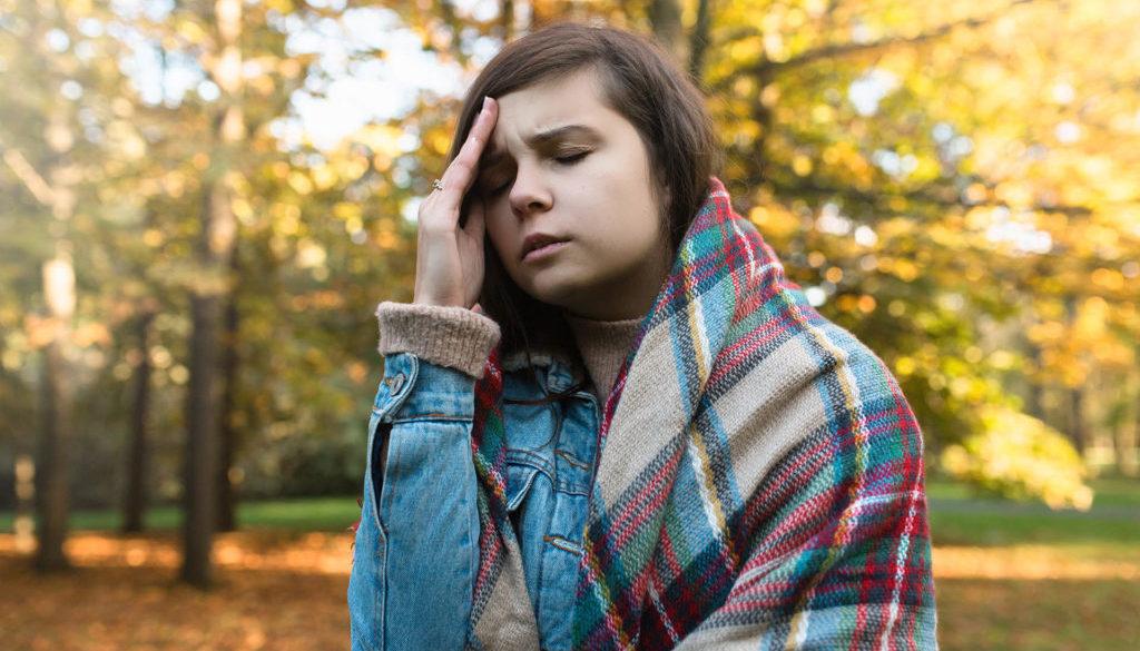 Młodą Dziewczynę Boli Głowa. Kolorowe Drzewa W Tle